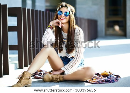 Funny stylish sexy smiling beautiful young hippie woman model in summer white fresh hipster clothes sitting in the street  - stock photo