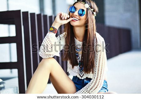 Funny stylish sexy smiling beautiful young hippie woman model in summer white fresh hipster clothes sitting in the street