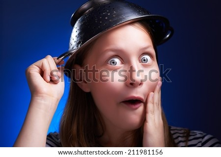 Funny surprised teen girl with a colander on her head - stock photo