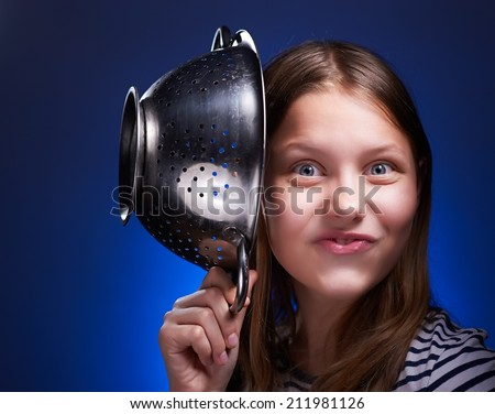Funny teen girl holding colander and grimacing - stock photo