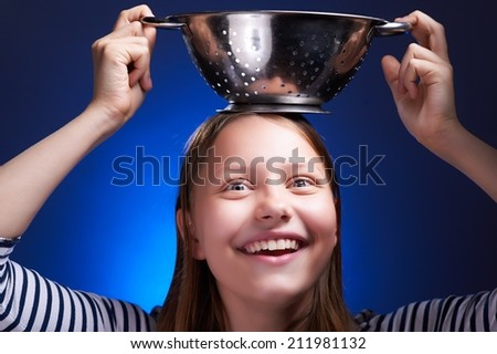 Funny teen girl holding colander on her head and laughing - stock photo