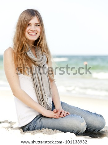 Funny teen girl sitting near the sea.