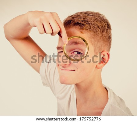 funny teenage boy with magnifier - stock photo