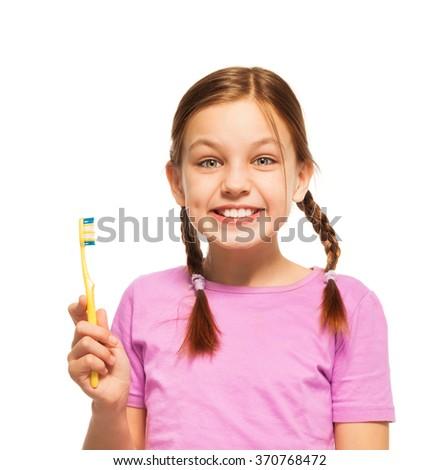 Funny teenage girl in pink tee brushing her teeth - stock photo