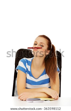 Funny teenage woman doing mustache from pen - stock photo