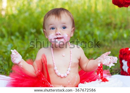 Funny toddler eating cake and shows cheerful emotions - stock photo