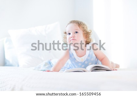 Funny toddler girl in a blue dress reading a book on a white bed - stock photo