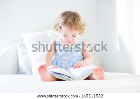Funny toddler girl in a blue dress reading a book on a white bed in a sunny bedroom - stock photo
