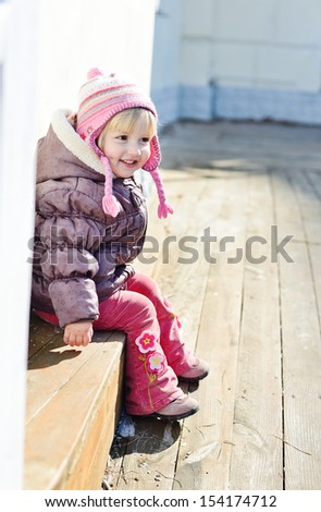 funny toddler girl sitting outdoors - stock photo