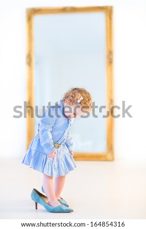 Funny toddler girl with beautiful curly hair wearing a blue dress is trying on her mother's high heels shoes in front of a big elegant mirror in a white bedroom - stock photo