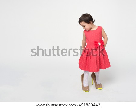 Funny toddler girl with black hair wearing a rad dress is trying on her mother's high heels shoes isolated on white background - stock photo