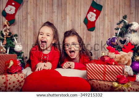 Funny toddler girls waiting for surprise from gift present box and making wish ready to celebrate New Year and Christmas at home  - stock photo