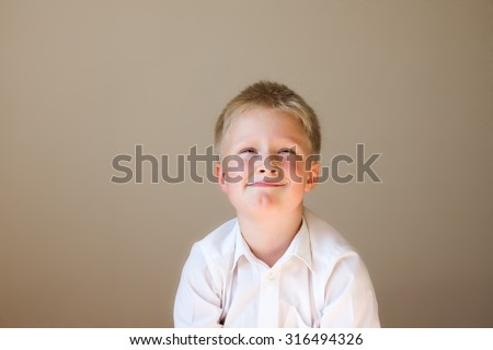 Funny tricky child (boy) thinking over grey background with copy space - stock photo