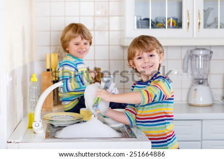 Funny twin boys helping in kitchen with washing dishes. Children having fun with housework. Indoors, siblings in colorful clothes. Selective focus - stock photo