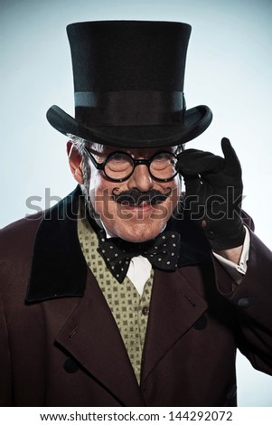 Funny vintage dickens style man with mustache and hat. Wearing glasses. Studio shot.