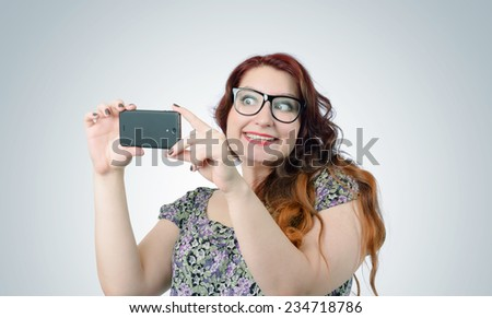 Funny viper girl with a smartphone on background  - stock photo