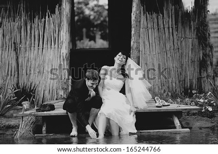 Funny wedding couple at the lake - stock photo