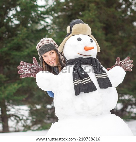 Funny winter portrait of beautiful young woman with snowman - stock photo