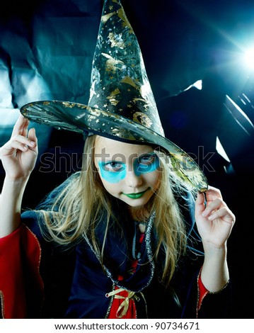 Funny witch girl in spooky robe hat on mystical dark background
