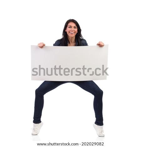 Funny woman holding white blank banner. Full length studio shot isolated on white. - stock photo