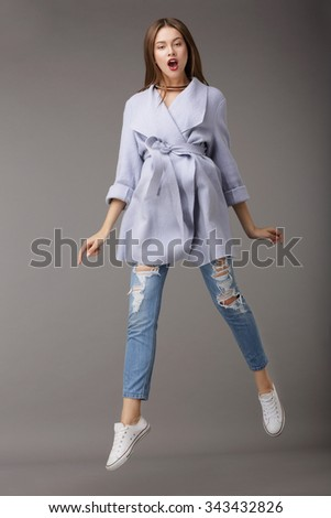 Funny Woman Jumping in Blue Coat - stock photo