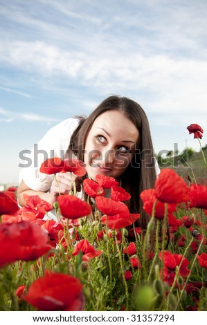 Funny woman smelling poppy flowers - stock photo