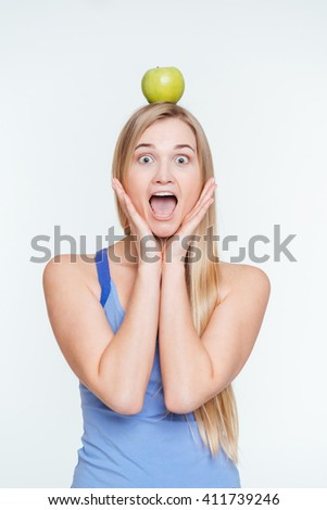 Funny woman with apple on head standing isolated on a white background - stock photo