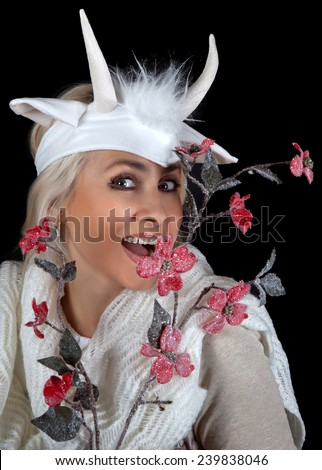 Funny woman with flowers and horns of a goat on a black background - stock photo