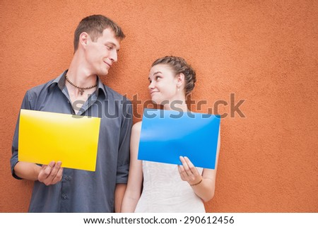 Funny young couple looking into eyes, holding yellow and blue frame at red background. Image ready for International, World Kissing Day 6 July, Valentine's Day, with copy space for any text or design - stock photo