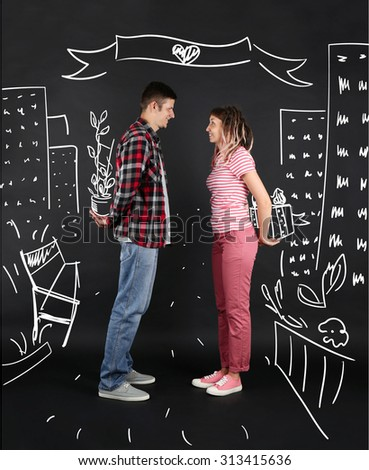 Funny young couple on black background - stock photo