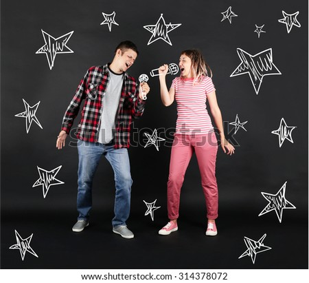 Funny young couple singing together with microphones, on black background - stock photo