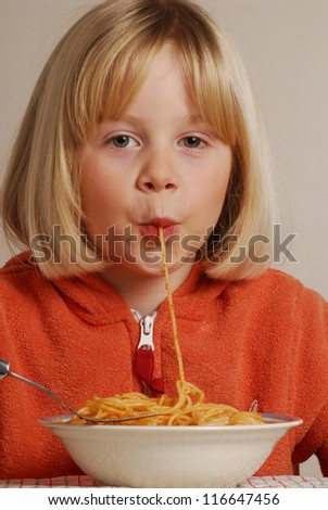 Funny young girl eating pasta. - stock photo