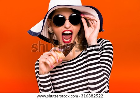 Funny young girl, wearing in striped blouse, black sunglasses and white hat, is holding plastic ice cream in her hand, like she is going to eat it, on orange background, in studio, waist up - stock photo
