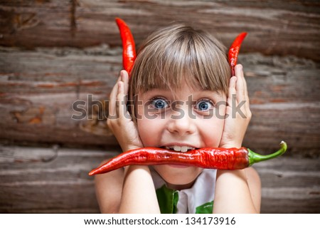 Funny young girl with a red hot chili pepper in her mouth showing red devil horns - stock photo