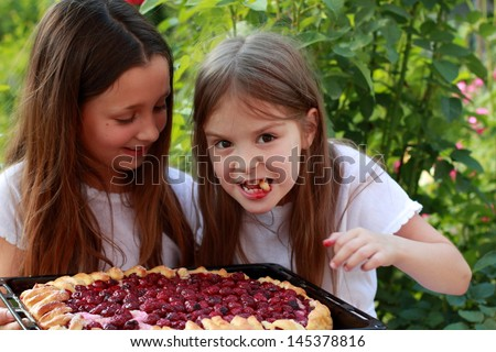 Funny young girls eat homemade cherry pie in the summer garden outdoors - stock photo