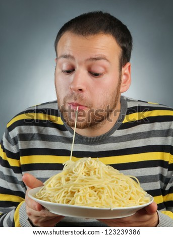 funny young man eating pasta - stock photo