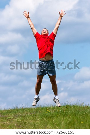 Funny young man high jumping in the field