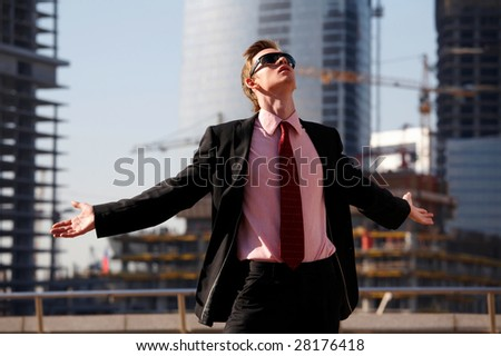 Funny young man with outstretched arms outdoors - stock photo