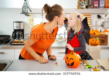 Funny young mother with daughter in bat costume eating colorfull halloween candy in decorated kitchen.  Halloween Candy is so good. Traditional autumn holiday - stock photo