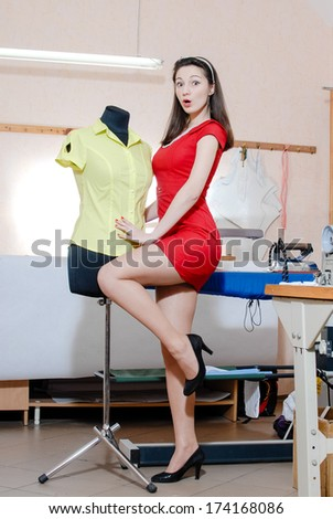 Funny young pinup woman with mannequin and measuring tape happy smiling & looking at camera