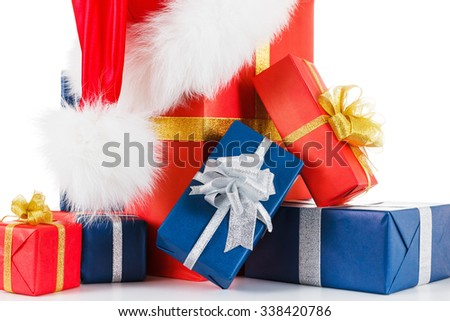Fur hat santa hat with gift boxes. Silver and gold ribbons. Isolated on white background closeup - stock photo