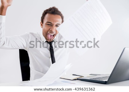 Furious african american businessman in office sick and tired of endless paperwork - stock photo