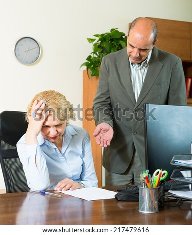 Furious boss screaming at his mature female assistant - stock photo