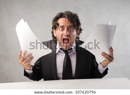 Furious businessman holding some documents - stock photo