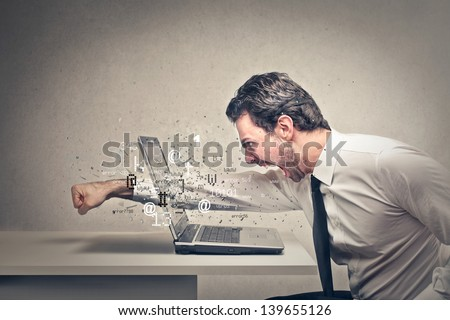 furious businessman throws a punch into the computer - stock photo
