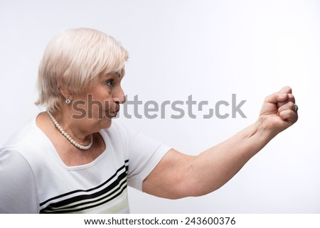 Furious elderly woman. Closeup side view portrait of angry elderly woman showing her fist up with negative facial expression while standing against white background - stock photo