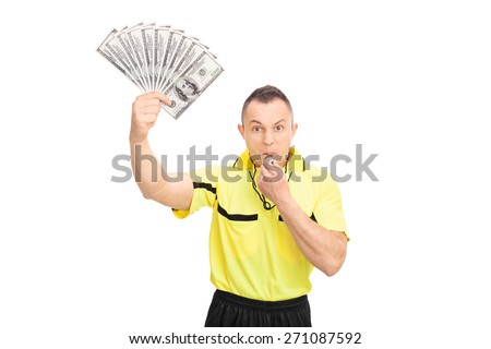 Furious football referee blowing a whistle, holding a stack of money and looking at the camera isolated on white background - stock photo