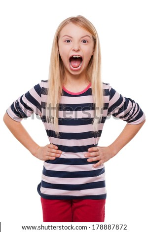 Furious little girl. Angry little girl shouting and holding hands on hip while standing isolated on white - stock photo