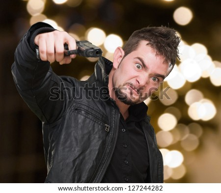 furious man pointing with a gun against an abstract light background