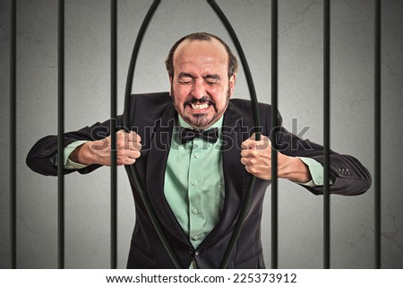 Furious strong middle aged businessman bending bars of his prison cell grey wall background. Life limitations, law violation infringement tax evasion consequences concept. Face expression emotion   - stock photo